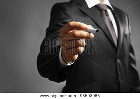 Businessman holding marker on gray background