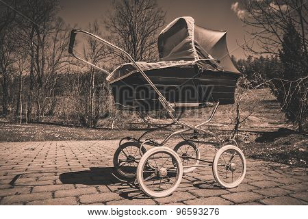 Retro style baby carriage outdoors on sunny day, black and white