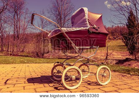 Retro style baby carriage outdoors on sunny day, red filter