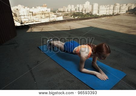 red haired lady does stretching during workout