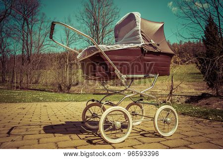 Retro style baby carriage outdoors on sunny day, green filter