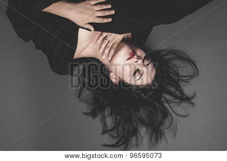 Death, gothic dark woman with large black cloth on gray background, Sadness