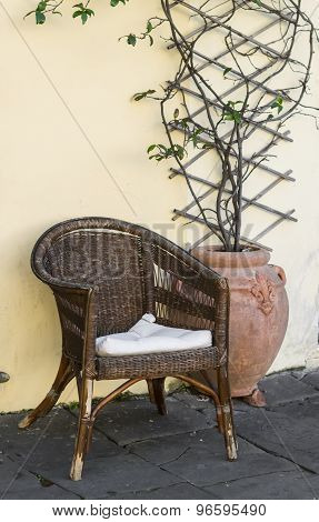 Old Wicker Rattan Chair And The Flower In Ceramic Vintage Pot Against The Yellow Wall, South Tyrol,