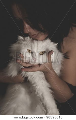 Cute, brunette woman with white Persian cat with long hair