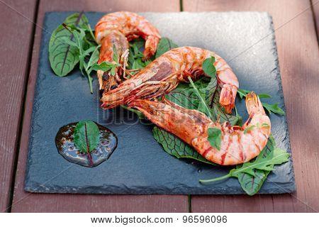 Grilled shrimps on square slate plate