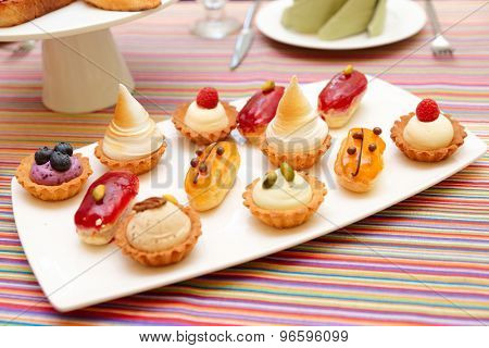 Set of small cakes on plate, close-up