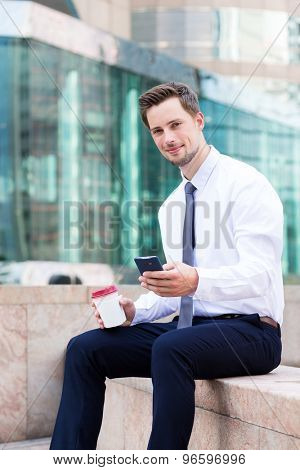 Businessman sitting outside with coffee cup and cellphone