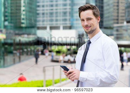 Businessman hold with mobile phone at outdoor