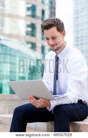 Caucasian businessman using the laptop computer at outdoor