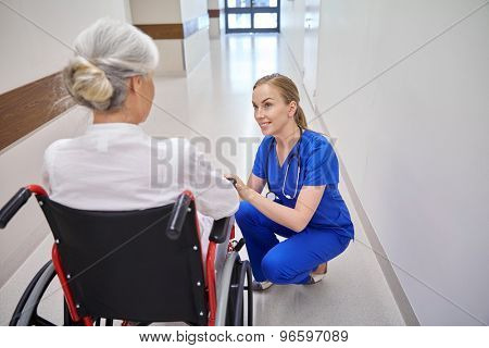 medicine, age, support, health care and people concept - happy nurse talking to senior woman patient in wheelchair at hospital corridor