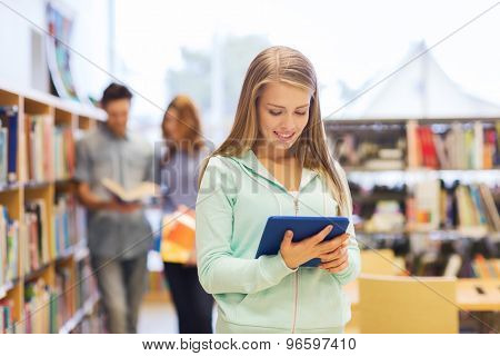 people, education, technology and school concept - happy student girl or woman with tablet pc computer in library