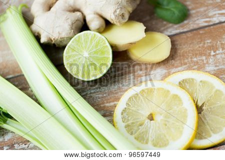 healthy eating, vegetarian food, culinary and diet concept - close up of ginger, celery and lemon on wooden table
