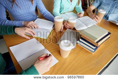 people, learning, education and school concept - close up of students hands with books or textbooks writing to notebooks and drinking coffee