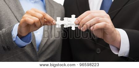 business concept - businessman and businesswoman holding puzzle pieces in office