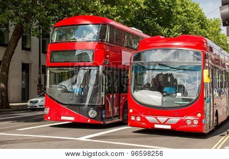 city life and public transport concept - city street with red double decker buses in london