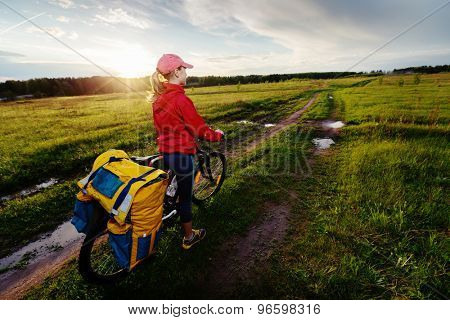 Lady hiker standing on the rural wet messy road with loaded bicycle