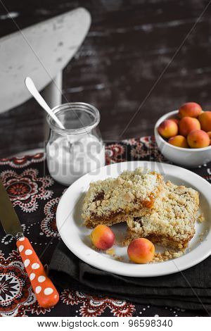 Pieces Of Apricot Pie On A White Plate, Bowl With Apricots And A Jar Of Natural Yoghurt On The Table