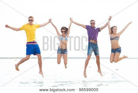 summer holidays, vacation, tourism, travel and people concept - group of happy friends holding hands and jumping on beach