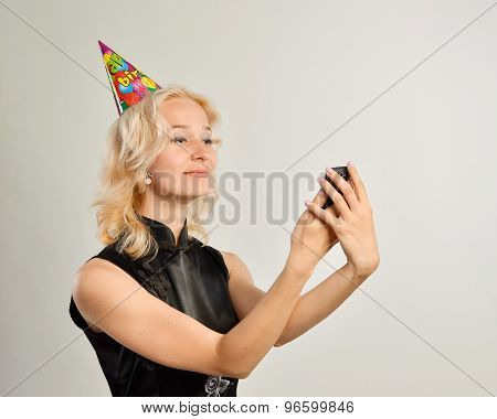 Portrait of a  young woman with a cell phone and birthday hat