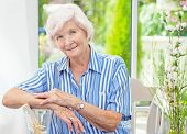 pic of beautiful senior woman  -  Beautiful senior woman sitting in her winter garden  - JPG