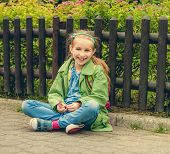 image of schoolgirls  - Little laughing schoolgirl  sitting on the street with her backpack - JPG