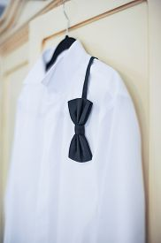 stock photo of bowing  - Wedding bright white shirt and black bow - JPG