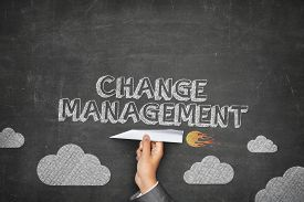 foto of change management  - Change management concept on black blackboard with businessman hand holding paper plane - JPG
