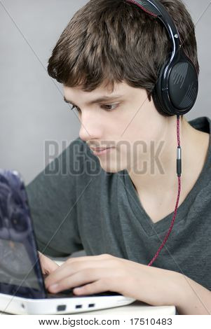 Teen Wearing Headphones Works On Computer