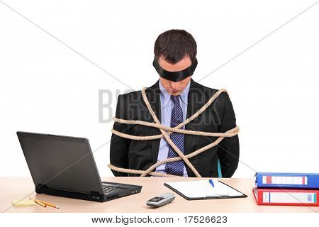 A businessman tied up with rope in his office isolated against white background