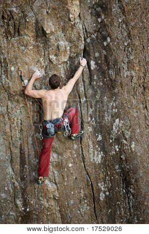 A male climber against a large rock face climbing lead against a magnificant landscape.