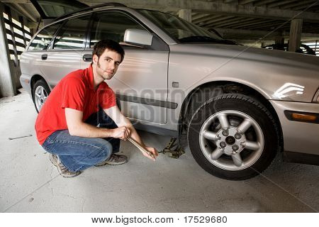 A male in a red shirt changing the front tire on a car