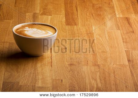 A warm specialty coffe on a wood table