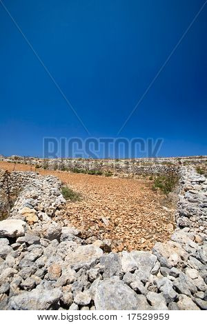 Farmland filled with rocks and red soil
