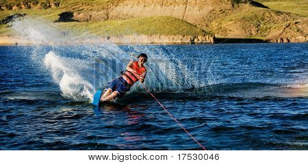 A male waterskiing on a lake in the evening