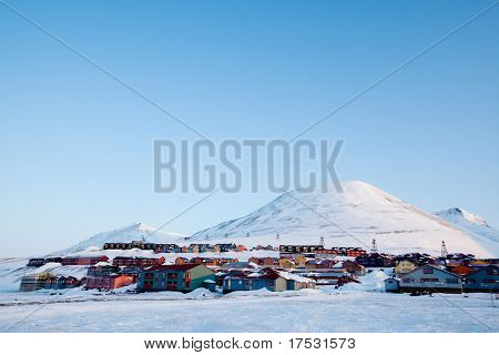 A detail of Longyearbyen, Svalbard, Norway.  A row of houses and a mountain in the distance.
