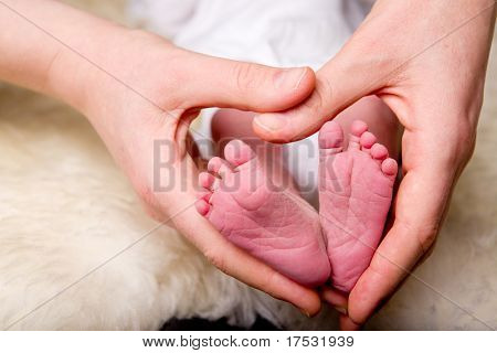 A mother's hands in the shape of a heart around a newborn baby's feet