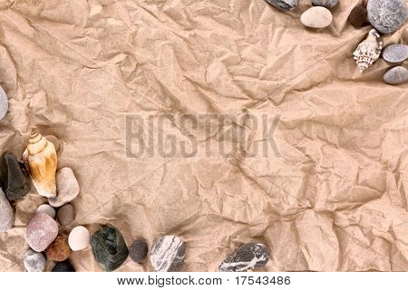 Brown crumpled paper and sea stones