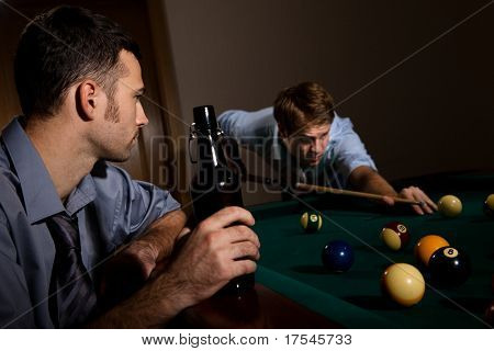 Young man playing snooker, concentrating with cue in hand, friend watching holding beer.?