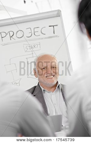 Smiling senior businessman presenting project at whiteboard, smiling.?