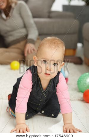 Porträt von niedlichen Babymädchen kniend auf Wohnzimmer Boden suchen beiseite.?