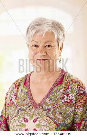 Portrait of elderly woman in colorful shirt, looking at camera, smiling.?