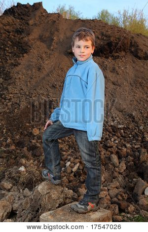 Little boy in blue jacket stands on earthen embankment at evening