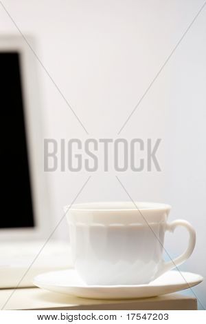 Photo of porcelain coffee cup with open laptop at background