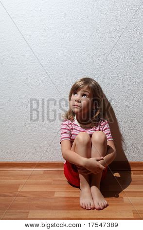 Little girl in casual clothes looks sad to corner, whence comes the light