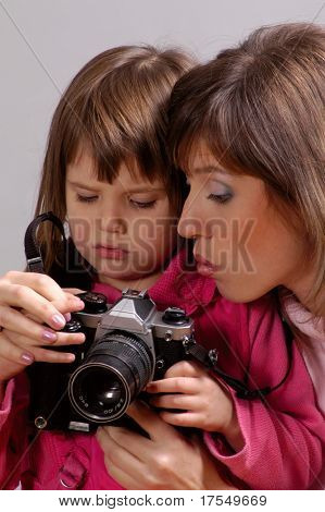 Mother teaching little daughter how to use camera