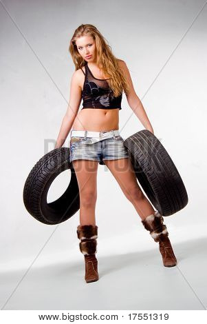 Lovely girl holding two car's tires