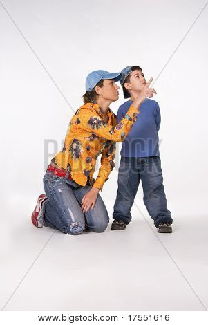 Young mother and son isolated on white background. Mother pointing outside with finger