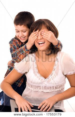 Mother and son playing hide and seek and working on laptop