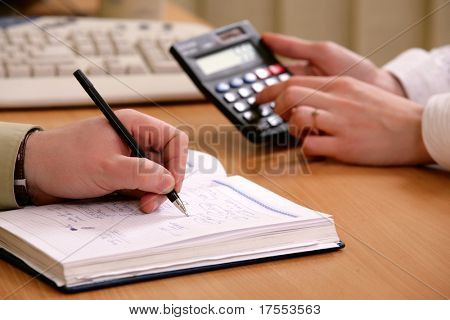 Close-up of office desktop with hands, calculator, papers and keyboard