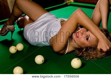 Beautiful model lying on green snooker table